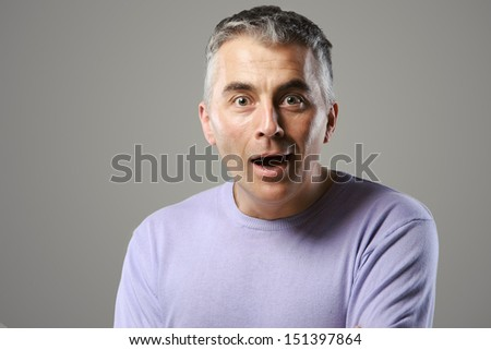 Portrait of casual man surprised on grey background