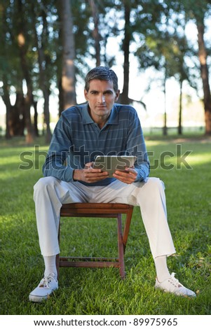 Portrait of casual middle aged man holding tablet PC - stock photo