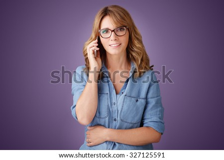 Portrait of casual professional woman holding in her hand a mobile phone and making call while standing at isolated background.