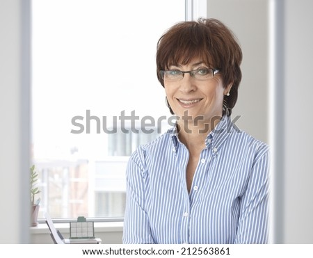 Portrait of casual senior caucasian businesswoman at office. Smiling, looking at camera, wearing glasses. - stock photo