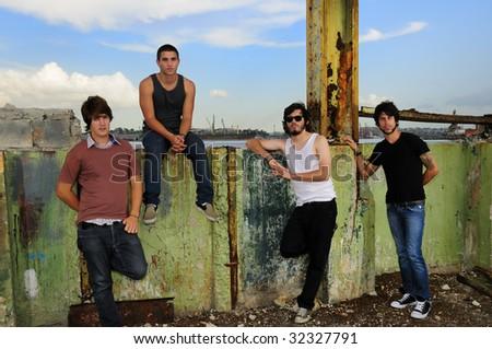 Portrait of casual team of friends posing on grunge urban scene - stock photo