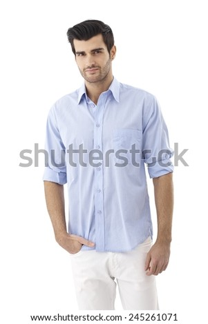 Portrait of casual young man in shirt, standing with hand in pocket, looking at camera. - stock photo