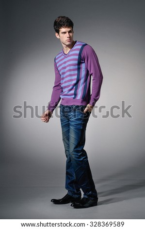 Portrait of casual young man in sweater walking in studio - stock photo