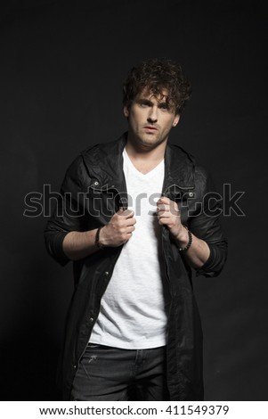 Portrait of casual young man over black background. Low key. - stock photo