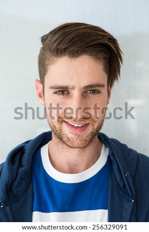 Portrait of casual young man smiling - stock photo