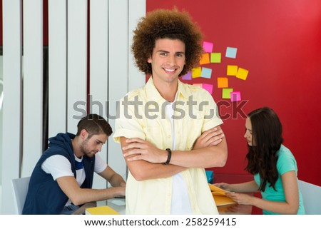 Portrait of casual young man standing with arms crossed in office - stock photo