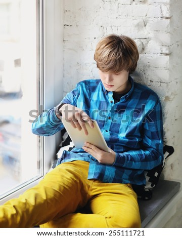 Portrait of casual young man using a digital tablet.  - stock photo
