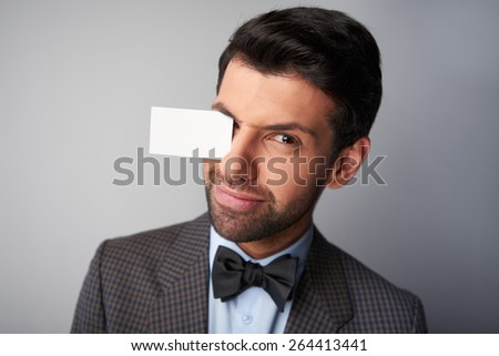 Portrait of casual young man wearing jacket and bow tie. Man winking and holding blank visiting card by eyebrow - stock photo