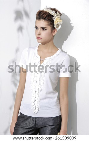 portrait of casual young woman standing on light background - stock photo