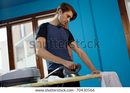 portrait of caucasian adult man ironing white shirt at home. Horizontal shape, low angle view, side view