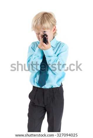 Portrait of Caucasian blond child aiming with black gun in hands, isolated on white background - stock photo