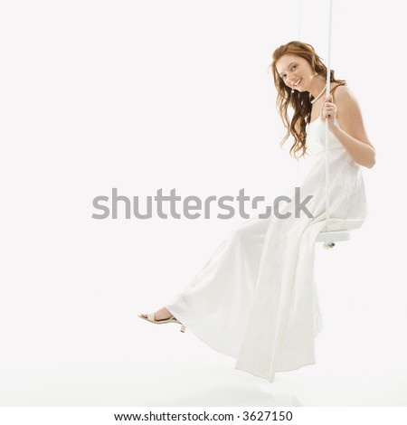 Portrait of Caucasian bride swinging on swing set. - stock photo