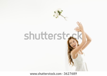 Portrait of Caucasian bride tossing bouquet behind her. - stock photo
