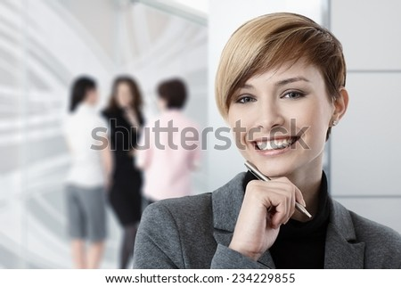 Portrait of caucasian businesswoman at office, colleagues in background.