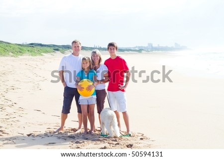 Portrait of Caucasian family of four and their family dog on beach - stock photo