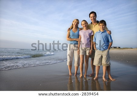 Portrait of Caucasian family of four posing on beach looking at viewer smiling. - stock photo
