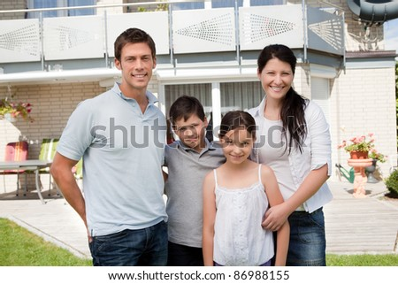 Portrait of caucasian family standing together in front of their new house - stock photo