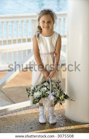 Portrait of Caucasian flower girl holding flower basket smiling.
