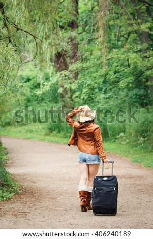 Portrait of Caucasian girl woman in leather jacket, blue denim shorts, straw hat, standing walking on country road wild forest with travel bag with her back to camera, wanderlust adventure vacation  - stock photo