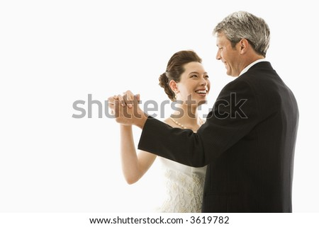 Portrait of Caucasian groom and Asian bride dancing. - stock photo