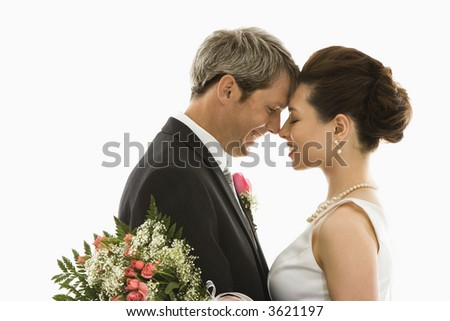 Portrait of Caucasian groom and Asian bride embracing - stock photo