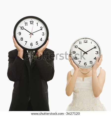 Portrait of Caucasian groom and Asian bride with clocks covering their faces.