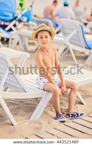 Portrait of caucasian happy baby (boy) in the hat. Child is smiling in summer day at the beach. Kid is enjoying ocean. - stock photo