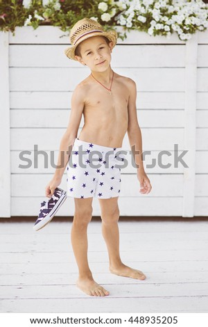 Portrait of caucasian happy baby (boy) in the straw  hat near swimming pool. Child is smiling in summer day. Kid is enjoying summer. Image has copyspace for text. Outdoor, close up. - stock photo