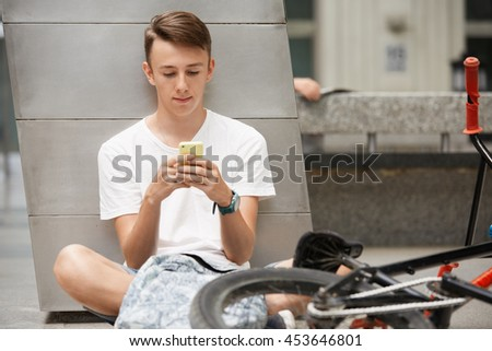 Portrait of Caucasian high school student in white T-shirt surfing the Internet using free wi-fi on cell phone while waiting for his girlfriend outside, sitting on the ground next to his BMX bicycle - stock photo