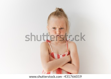 Portrait of Caucasian kid with blond hair and crossed hands on her chest. Angry female child with spoiled look demonstrating bad vibes. Negative emotions and offence. - stock photo