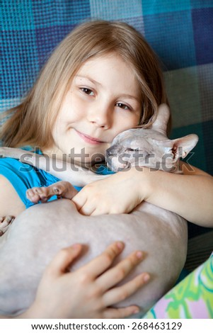 Portrait of Caucasian little girl hugging a bald cat, close up view - stock photo
