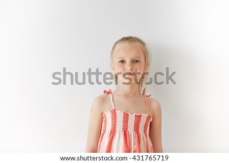 Portrait of Caucasian little girl in sundress looking at camera. Innocent and carefree female kid with blond hair is calm and restful standing on white background. Cute infant is relaxed. - stock photo