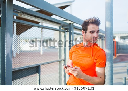 Portrait of caucasian male runner hold mobile phone in the hands while taking break after active training at sunny afternoon, young sports man using mobile phone while rest after workout outdoors - stock photo