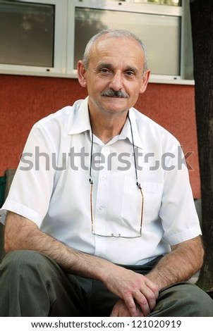 portrait of caucasian mature man smiling outdoors - stock photo