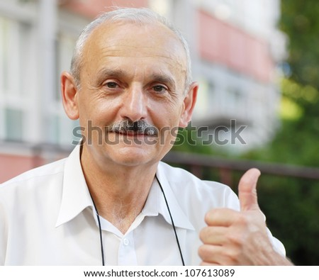 portrait of caucasian mature man with thumb up hand sign - stock photo
