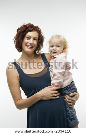 Portrait of Caucasian mid-adult attractive pregnant woman standing, holding female toddler on hip and other hand on belly, looking at viewer and smiling. - stock photo