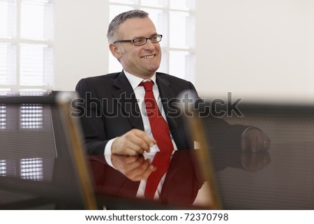 Portrait of caucasian mid adult business man talking to colleagues in meeting room. Horizontal shape, side view, copy space - stock photo