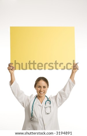 Portrait of Caucasian mid-adult female doctor holding up blank yellow sign smiling and looking at viewer. - stock photo