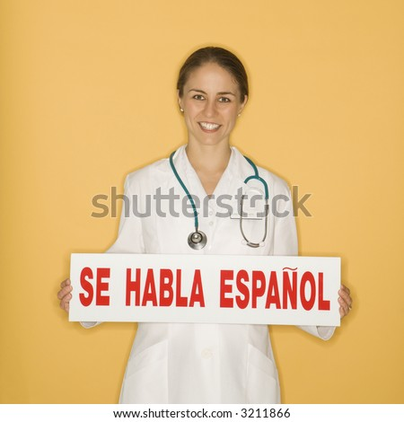 Portrait of Caucasian mid-adult female doctor holding up se habla espanol sign against yellow background smiling and looking at viewer. - stock photo