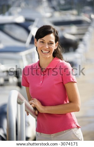 Portrait of Caucasian mid-adult female smiling at camera and holding railing at harbor.