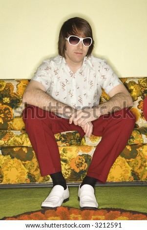 Portrait of Caucasian mid-adult man wearing sunglasses sitting on colorful retro sofa. - stock photo