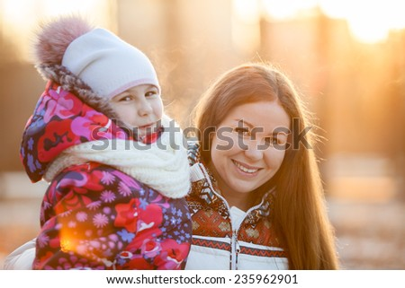 Portrait of Caucasian mother with a child at winter, a frosty evening, sunshine, sunset - stock photo
