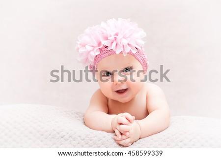 portrait of caucasian newborn with pink flower woolen hat - stock photo