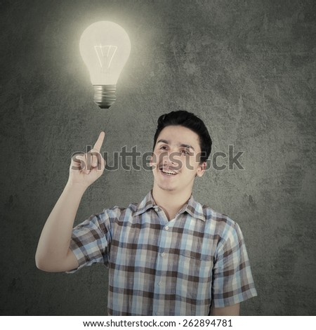 Portrait of caucasian person wearing casual shirt and pointing at bright lightbulb