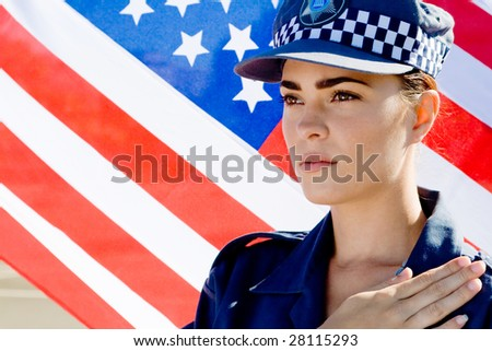 Portrait of Caucasian policewoman pledging allegiance with USA flag as background