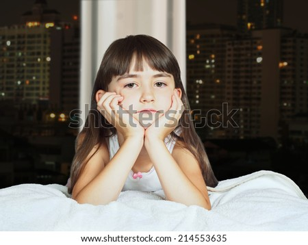 Portrait of caucasian sad girl child kid on background of window with night town - stock photo