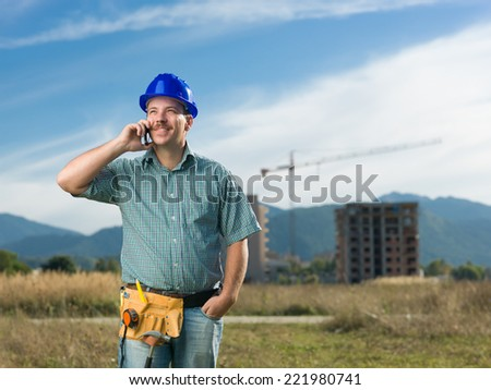 portrait of caucasian smiling engineer talking on phone on residential construction site
