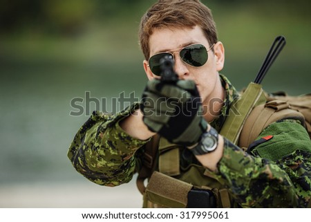 portrait of caucasian soldier with canadian camouflage pointing with pistol over outdoor background - stock photo