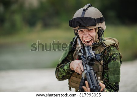 portrait of caucasian soldier with canadian camouflage pointing with rifle over outdoor background - stock photo