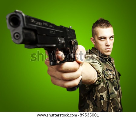 portrait of caucasian soldier with jungle camouflage pointing with pistol over green background - stock photo